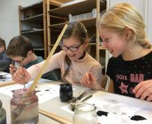 Leerlingen maken schilderij van inkt op water en olie