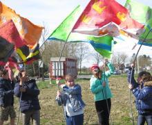 Kinderen zwaaien met zelfgemaakte vlaggen